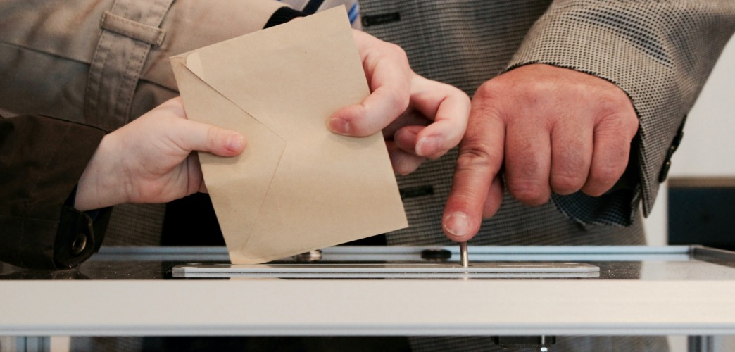 a person putting a ballot into the box.
