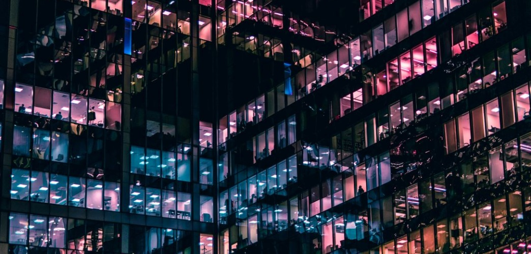 a series of windows lit up in pick and purple hues in a business building at night.