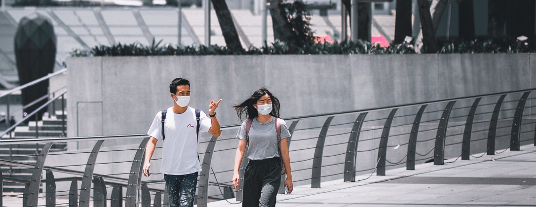 two pedestrians walking on a sidewalk wearing personal protective masks to prevent coronavirus spread.