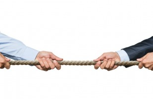 Two businesspersons tugging at a rope.