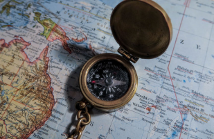 an open compass laying on a map of the world.