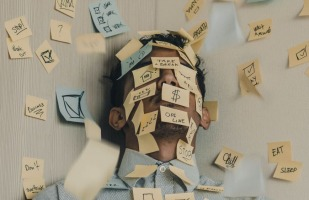 a man covered in sticky notes with advice on them.
