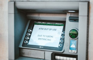 "An ATM whose screen displays "" ATM out of use due to social distancing"""