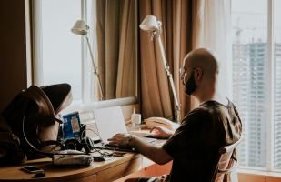 Man working from home on his laptop, at his desk.
