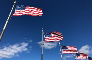 5 american flags flying in the sky on a beautiful day.